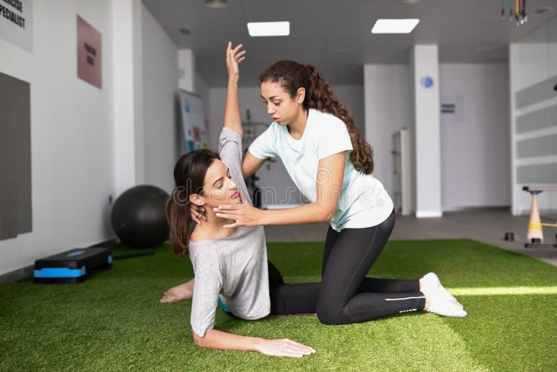 Fysisk terapeut som hjälper den unga caucasian kvinnan med övning royaltyfri foto