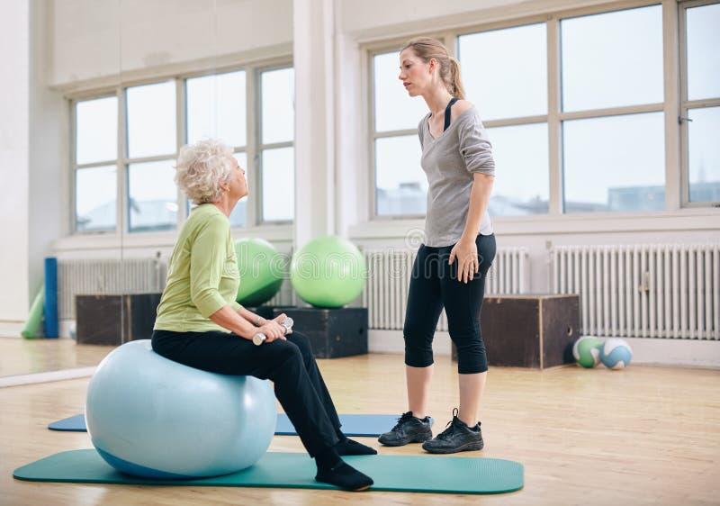 Fysisk terapeut som instruerar en hög kvinna på rehab arkivfoton