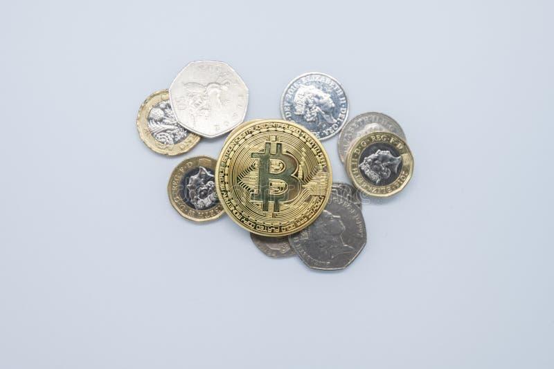Fysiska guld- Bitcoin som överst lägger av gamla engelska pengar för slätt royaltyfri foto