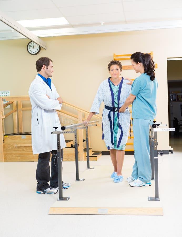Fysiska terapeuter som in hjälper den kvinnliga patienten fotografering för bildbyråer