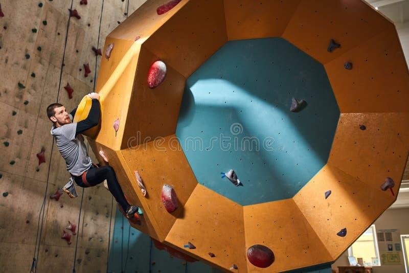Fysiskt nedsatta manliga bergsbestigaredrev inomhus på den bouldering idrottshallen royaltyfri fotografi