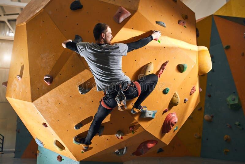 Fysiskt utmanad klättrare som försöker att nå överkanten av den konstgjorda klättraväggen royaltyfria foton