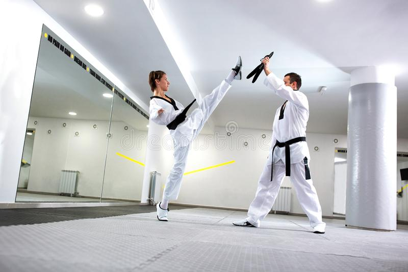 Fysiskt utmanad ung kvinna i Taekwondo som öva en hög spark royaltyfri foto
