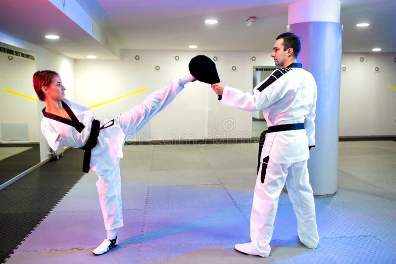 Fysiskt utmanad ung kvinna i Taekwondo som öva en hög spark royaltyfria foton