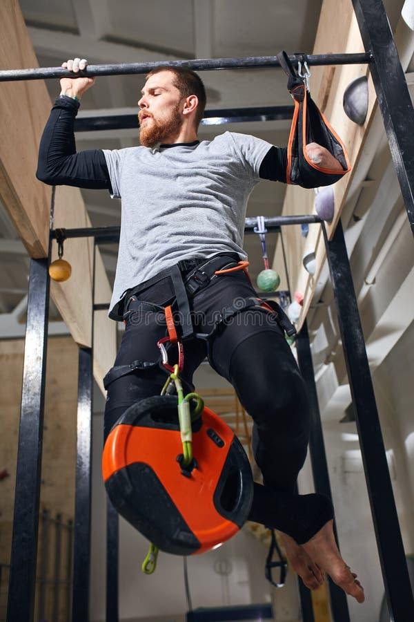 Fysiskt utmanad ung man som gör handtag upp övningar med den tunga påfyllningen arkivfoto