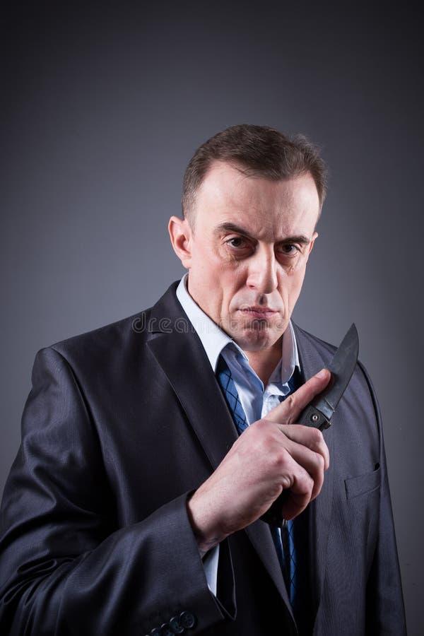 Gángster de sexo masculino en un traje de negocios con un cuchillo fotografía de archivo libre de regalías