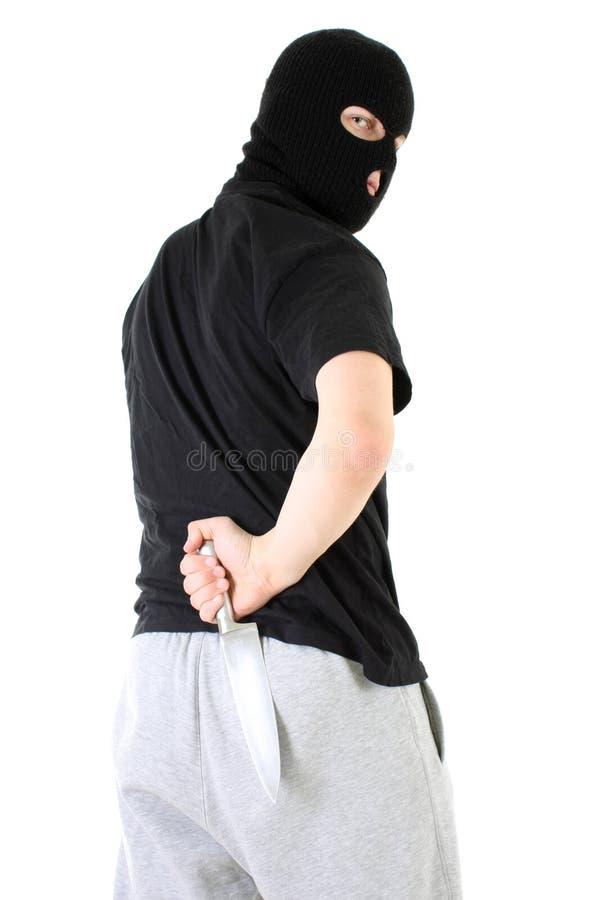 Gángster en máscara con el cuchillo fotografía de archivo
