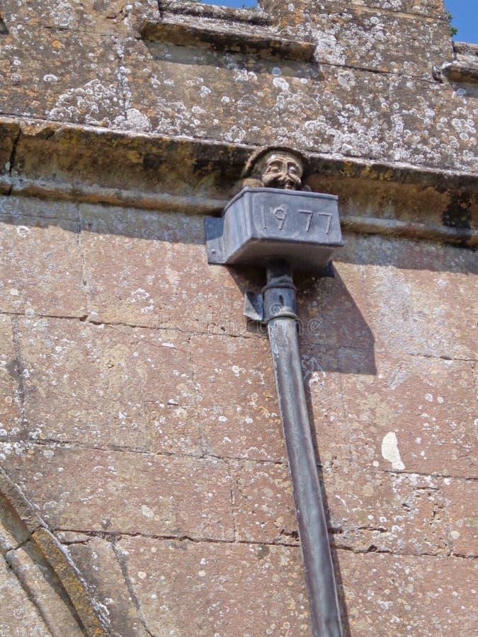 Gárgula inglesa no dreno na igreja velha rural da vila, quase uma ruína fotografia de stock