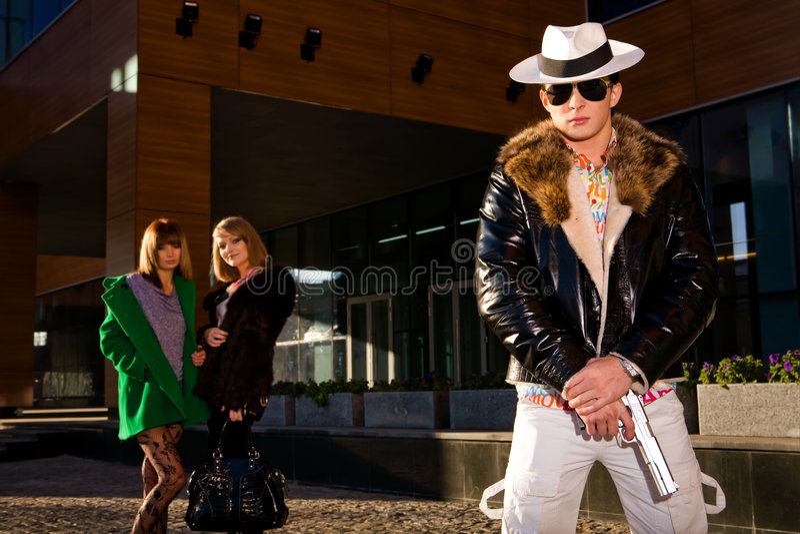 Gângster à moda com um injetor e as duas mulheres novas foto de stock royalty free