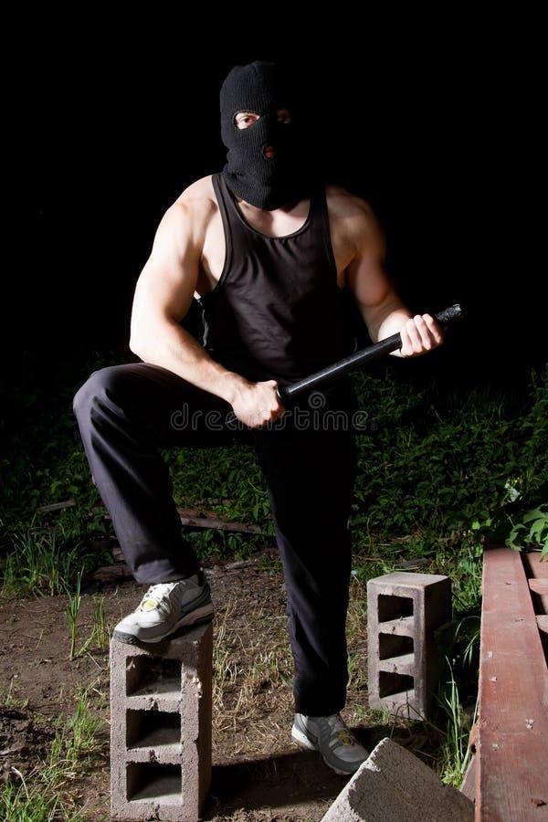 Gângster com bastão ao ar livre na noite fotos de stock