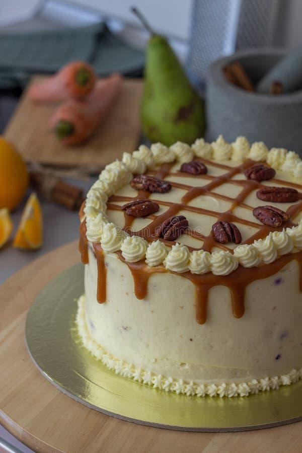 Gâteau à la carotte fait maison avec le givrage de fromage fondu, la sauce à caramel et l'écrimage de noix de pécan image libre de droits
