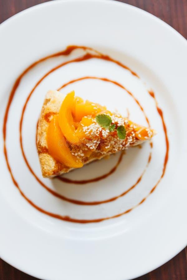 Gâteau au fromage avec le caramel et les pêches d'un plat blanc images libres de droits