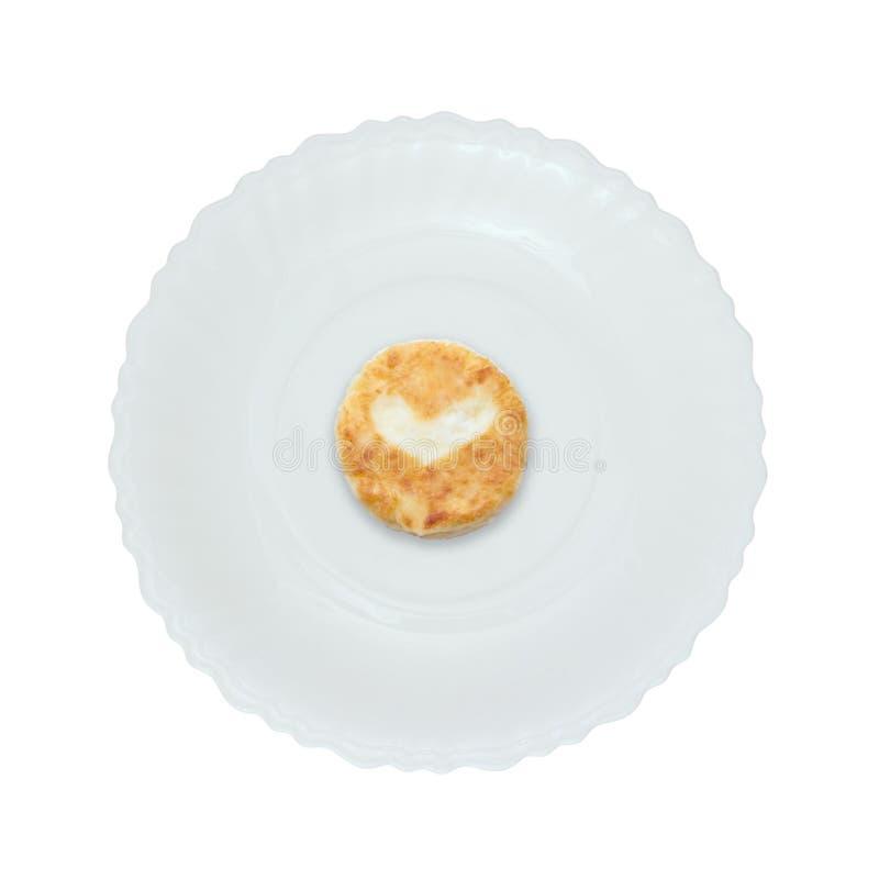 Gâteau au fromage avec le coeur d'un plat blanc D'isolement image stock