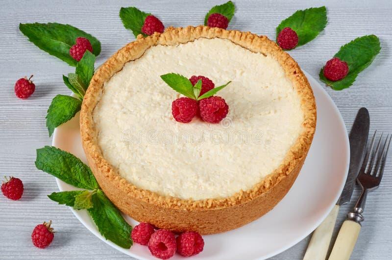 Gâteau au fromage avec les baies fraîches du plat blanc décoré des framboises, des feuilles en bon état, du couteau et de la four photo libre de droits