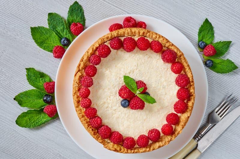 Gâteau au fromage classique de New York avec les framboises fraîches, les myrtilles et les feuilles en bon état du plat blanc sur photo stock
