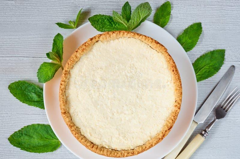 Gâteau au fromage classique de New York du plat blanc décoré des feuilles en bon état fraîches sur le fond gris de cuisine image stock