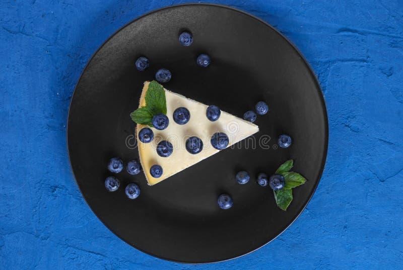 Gâteau au fromage classique de vue supérieure avec les myrtilles et la menthe d'un plat noir Fond bleu en pierre images libres de droits