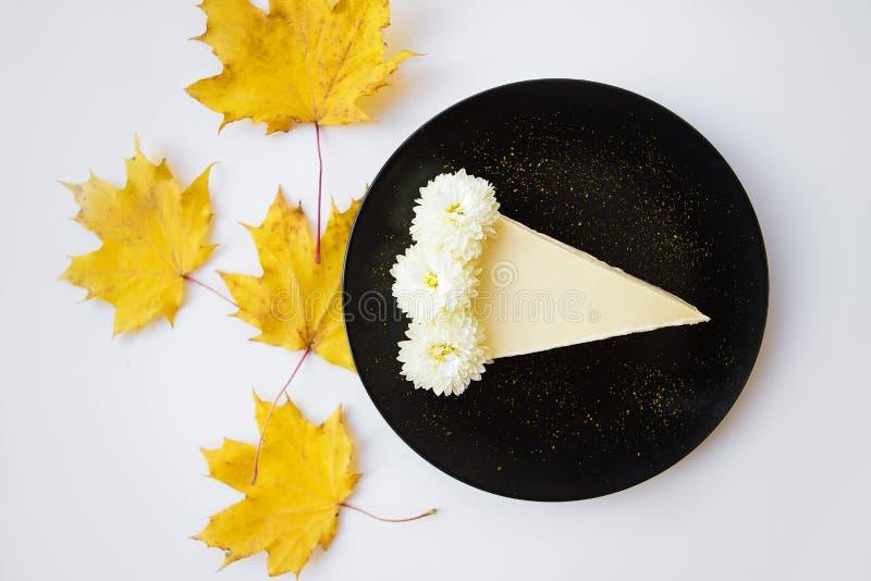 Gâteau au fromage crémeux d'un plat noir décoré des feuilles jaunes d'érable photos stock