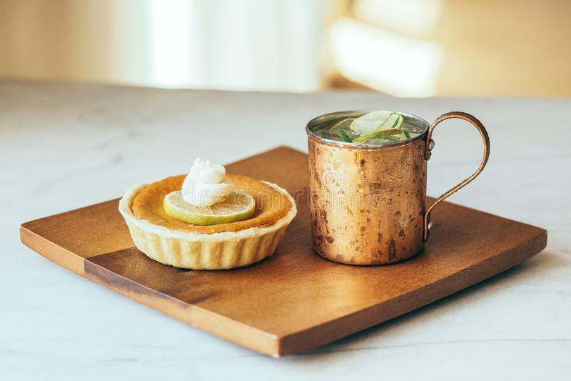 Gâteau au fromage de citron dans le plat en bois décoré d'une tranche de citron et de tasse de cuivre avec les tranches de citron image stock