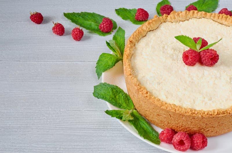 Gâteau au fromage fait maison avec les baies fraîches du plat blanc décoré des framboises, feuilles en bon état sur le fond gris photographie stock