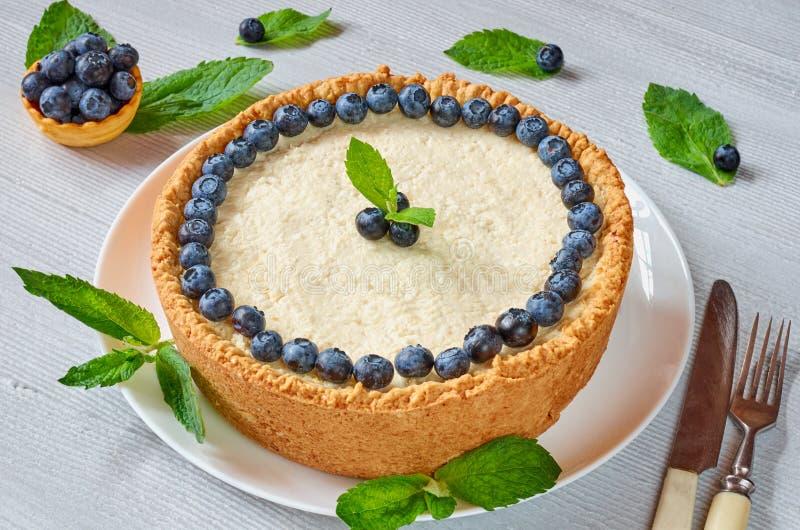 Gâteau au fromage fait maison avec les baies fraîches du plat blanc décoré des myrtilles, de la menthe, du couteau et de la fourc image stock