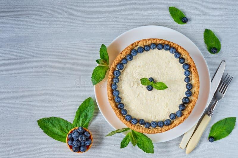 Gâteau au fromage fait maison avec les baies fraîches du plat blanc décoré des myrtilles, feuilles en bon état sur la table grise photos stock