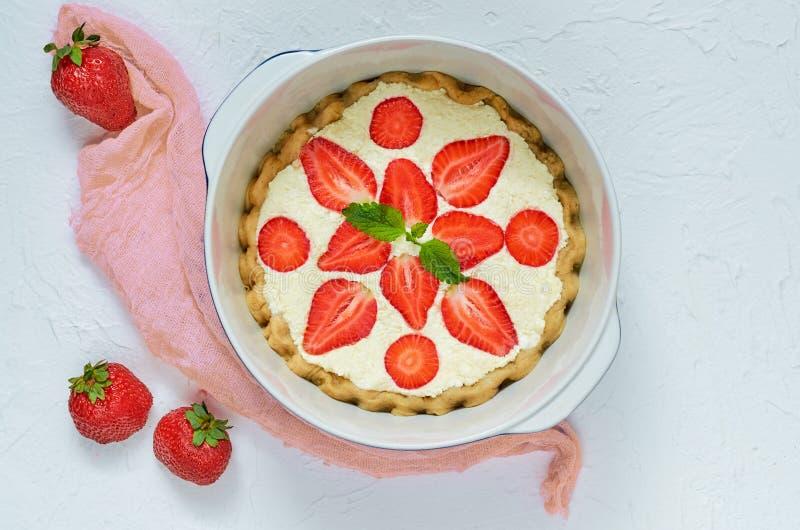 Gâteau au fromage fait maison dans un plat de cuisson sur le fond blanc Tarte crue saine végétarienne décorée des feuilles en bon photo libre de droits