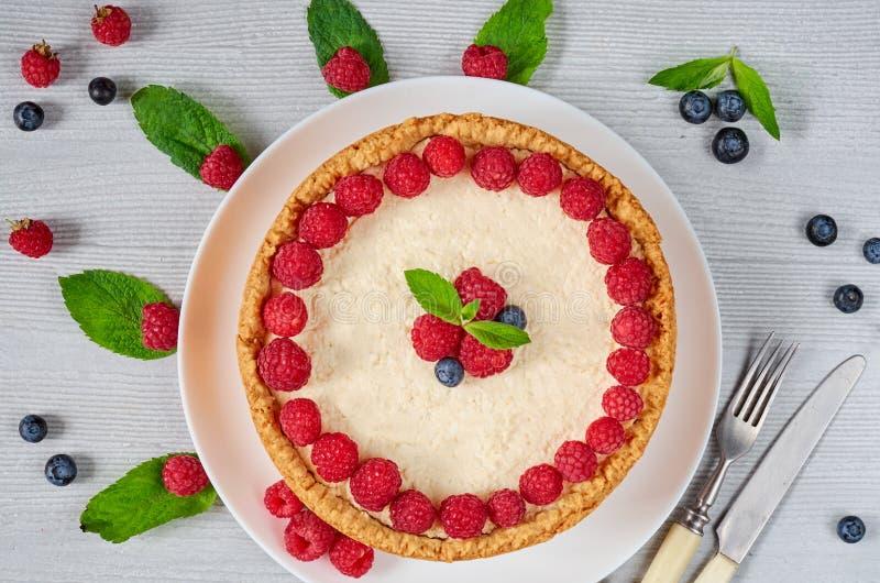 Gâteau au fromage fait maison de framboise du plat blanc décoré des baies fraîches, des feuilles en bon état, du couteau et de la images libres de droits