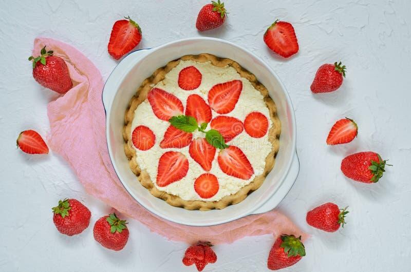Gâteau au fromage frais fait maison de fraise dans un plat de cuisson sur le fond blanc Tarte crue saine végétarienne avec des fr photo stock