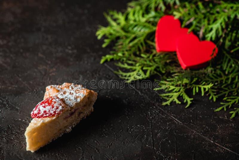 Gâteau au fromage le jour du ` s de Valentine avec la fraise, les coeurs de kiwi sur le sapin et le fond foncé photos stock