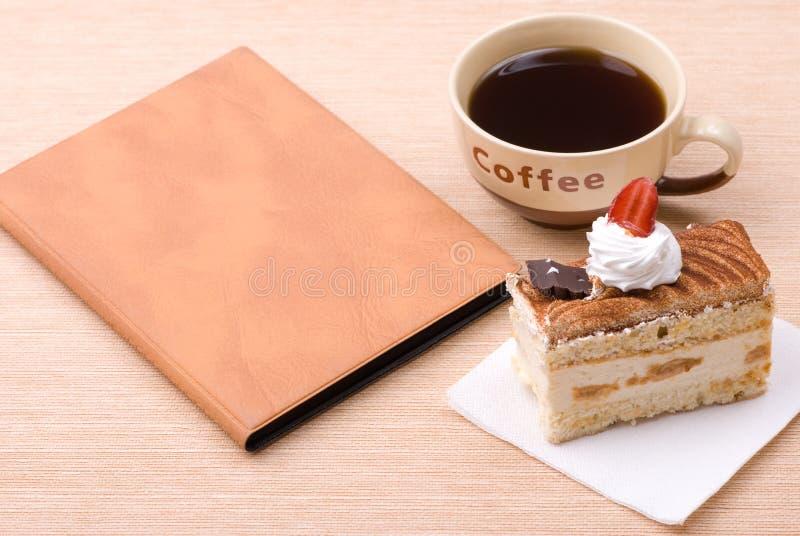 Gâteau avec la cuvette du café et du livre photos stock