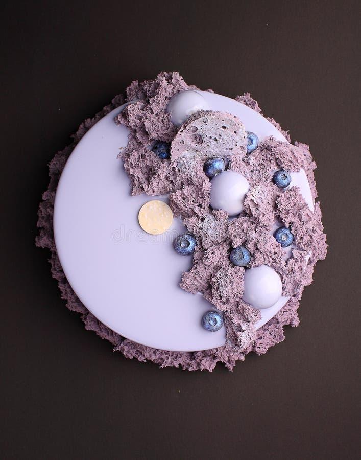 Gâteau avec la mousse de mûre dans le lustre de miroir décoré d'un biscui moléculaire photographie stock