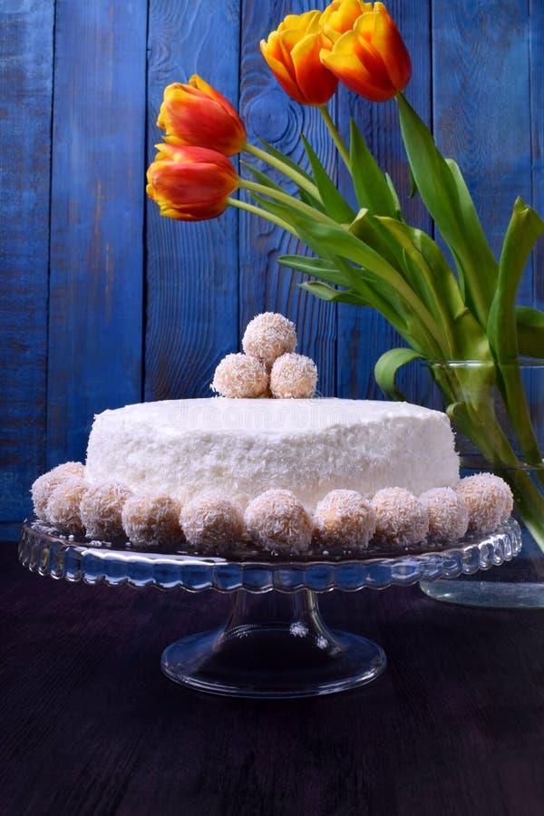 Gâteau avec les flocons fouettés de fromage fondu et de noix de coco d'un plat en verre de gâteau image stock