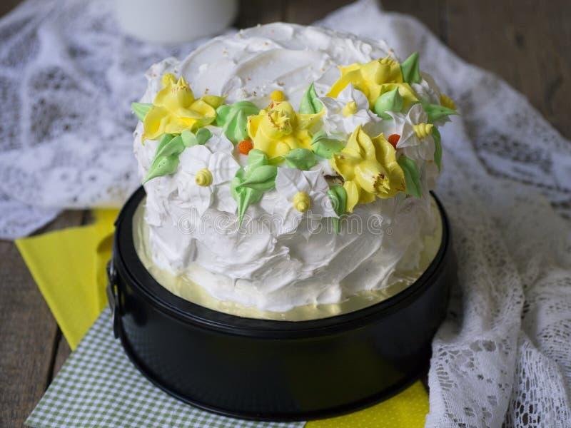 Gâteau blanc décoré des fleurs crèmes de ressort - jonquilles - sur le fond en bois avec le tissu de dentelle Vintage, rétro Cade photo libre de droits