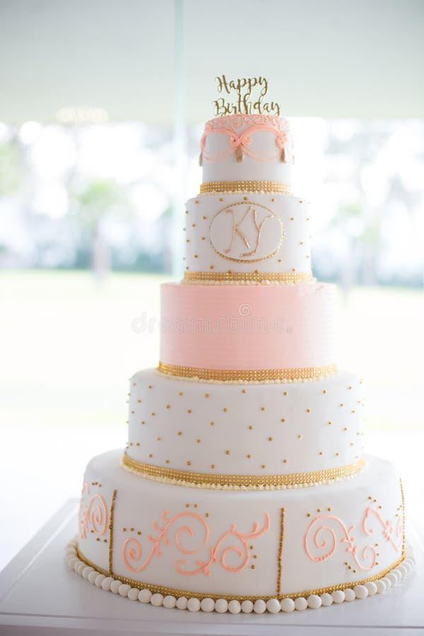 Gâteau blanc d'anniversaire et rose cinq-à gradins photo stock
