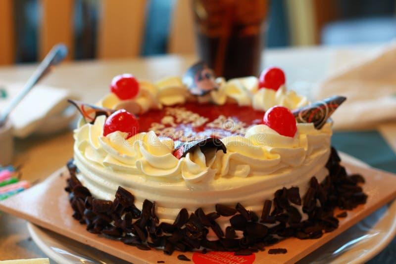Gâteau blanc de yaourt de cerise de chocolat décoré des fruits frais et du gros morceau de chocolat photographie stock libre de droits