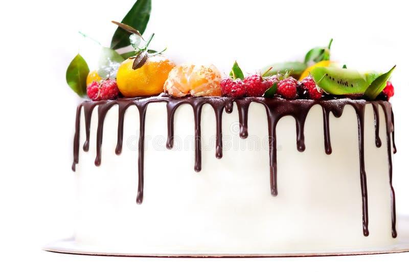 gâteau blanc trempé en chocolat et décoré des baies sur un fond blanc d'isolement images stock