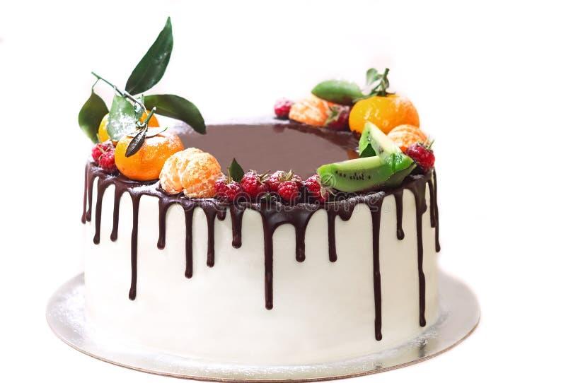 gâteau blanc trempé en chocolat et décoré des baies sur un fond blanc d'isolement images libres de droits