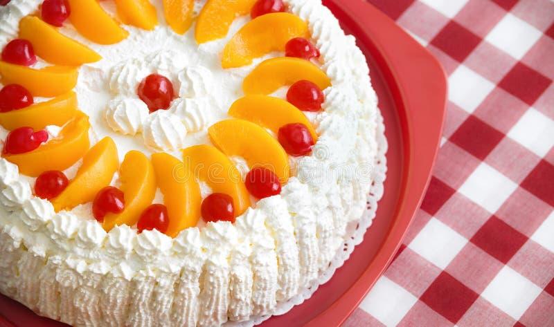 Gâteau crème avec des pêches et des cerises image libre de droits