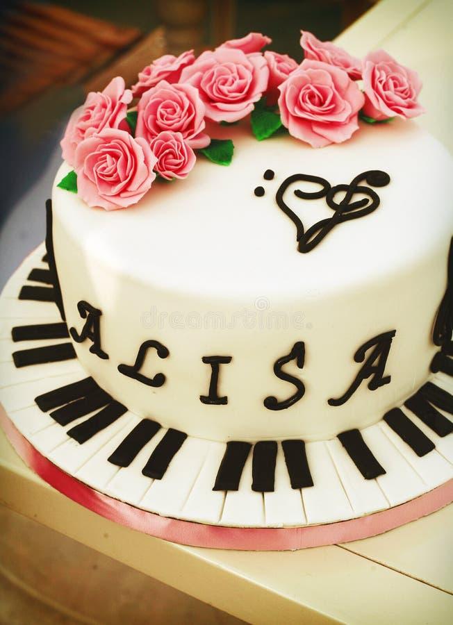 Gâteau crémeux avec les clés de piano, la clef triple et les roses photographie stock libre de droits