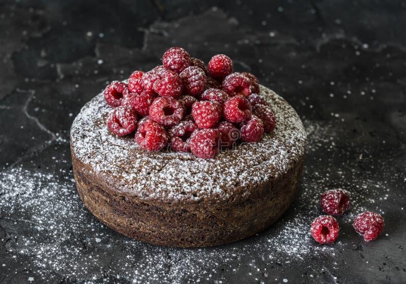 Gâteau d'écrou de chocolat avec la framboise fraîche sur le fond foncé Dessert d?licieux images stock