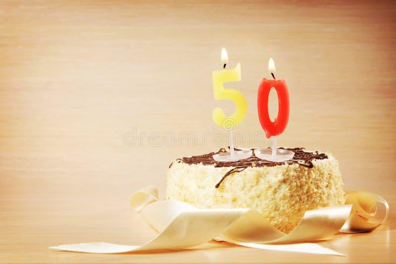 Gâteau d'anniversaire avec la bougie brûlante comme numéro cinquante image libre de droits
