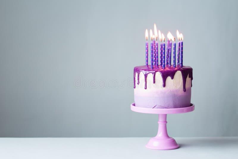 Gâteau d'anniversaire avec le glaçage d'égouttement et les bougies pourpres photos libres de droits