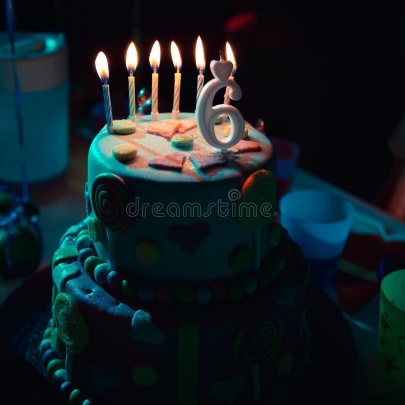 Gâteau d'anniversaire avec les bougies et l'âge brûlants 6 bougies à l'arrière-plan foncé avec des sucreries en décor images stock