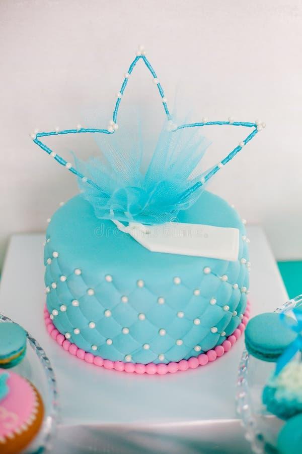 Gâteau d'anniversaire bleu et rose avec la grande couronne de perles pour peu de bébé et les décorations pour la partie photo stock