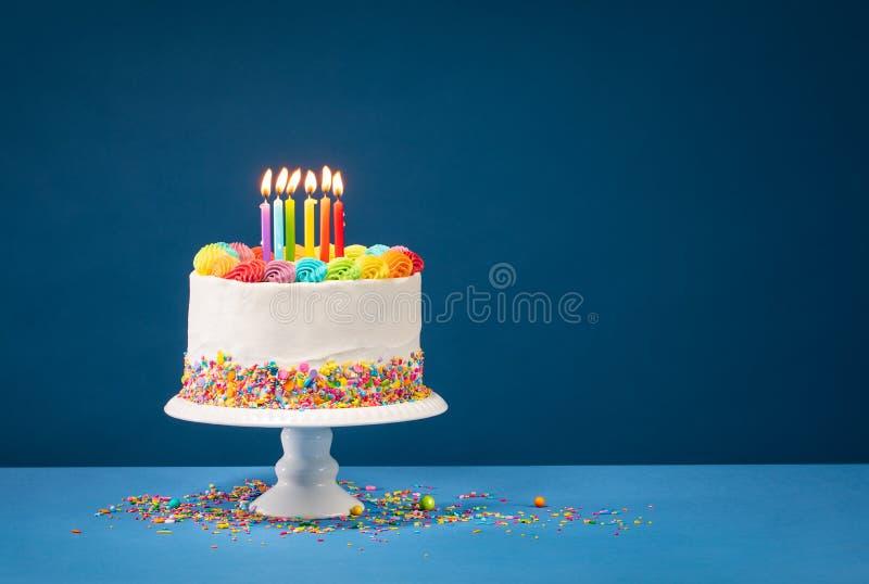 Gâteau d'anniversaire coloré au-dessus de bleu photos stock