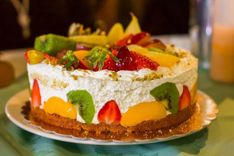 Gâteau d'anniversaire complètement de crème et de fruit frais images libres de droits