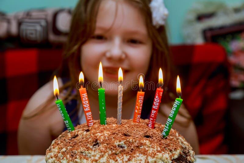 Gâteau d'anniversaire de soufflement de bougies de petite fille avec des bougies images libres de droits