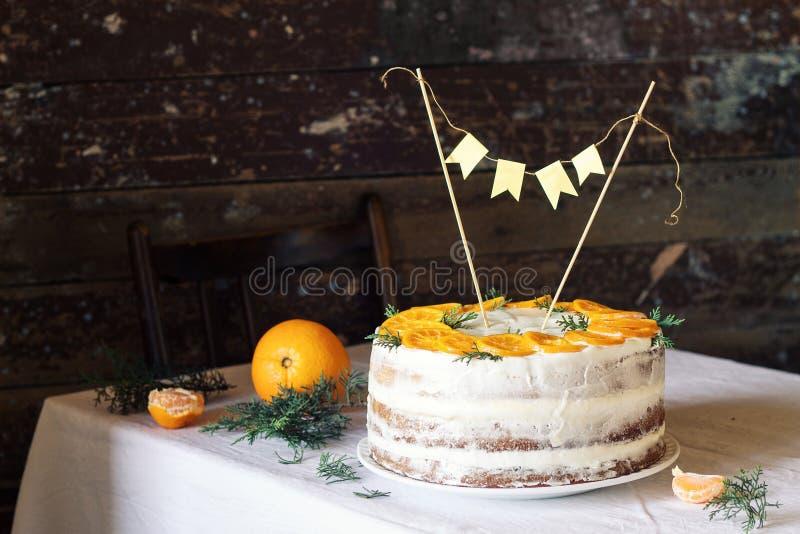 Gâteau d'anniversaire pour un anniversaire en hiver avec de la crème et des oranges photos stock