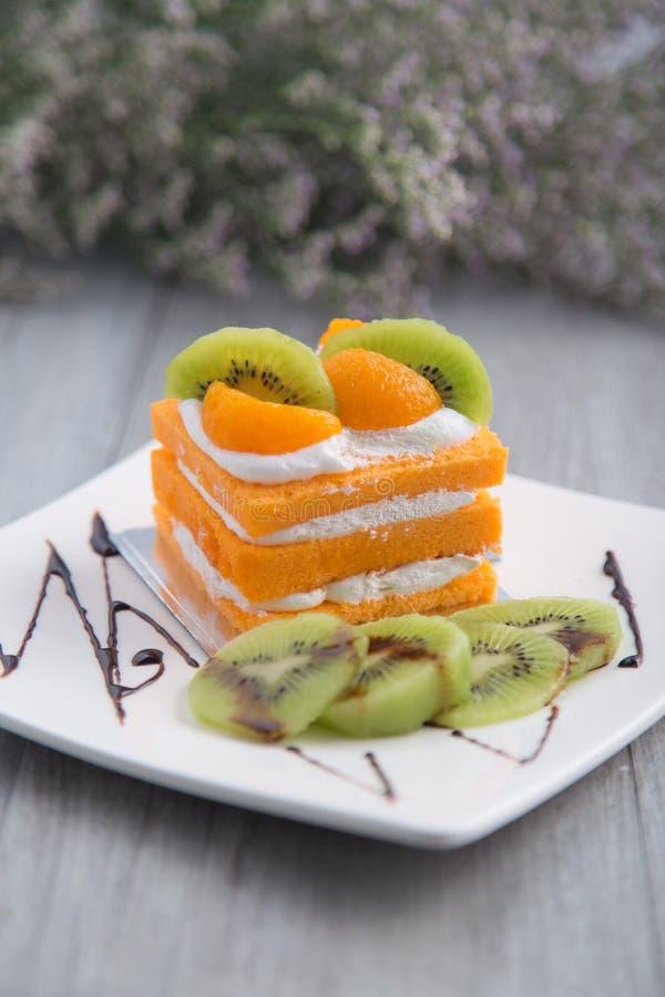 Gâteau d'orange et de kiwi sur le fond en bois images libres de droits